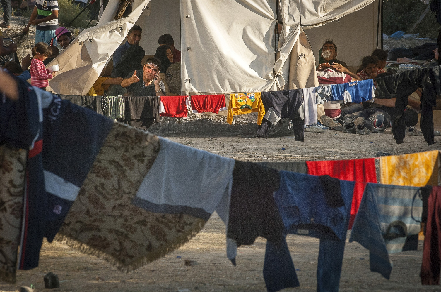 Tents in Moria Registration Camp, Lesbos, Greece. Mobile communication is essential for the refugees. Keeping contact with those who have travelled to Europe before them provides them with information on what to expect, which roads are still open, which train routes to take. This information is likewise passed on to those leaving Turkey, and down the line to Syria, Iraq, Afghanistan etc.