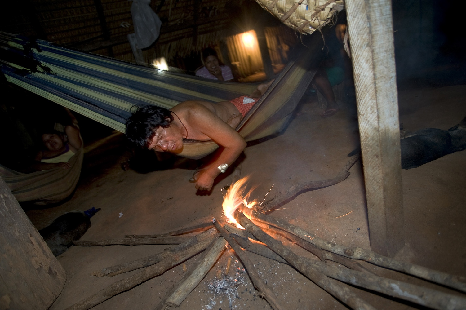 "Gasmasakaka Surui keeps the fire going at Lapetanha with in the ""7th September Indian Reserve"" Rondonia, Brazil."