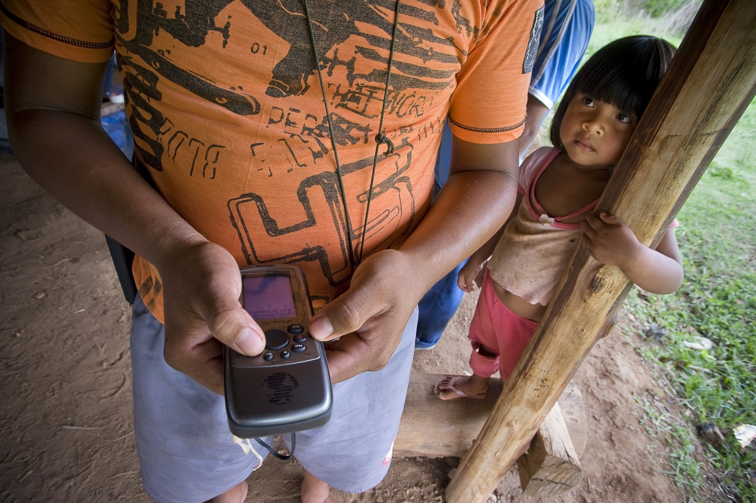 "Mopidmore (23) Surui holds the GPS device he will be taking into the rainforest for 15 days while his daughter Soeytxer(4) looks on.Lapetanha, Rondonia, Brazil at the ""7th September Indian Reserve""."