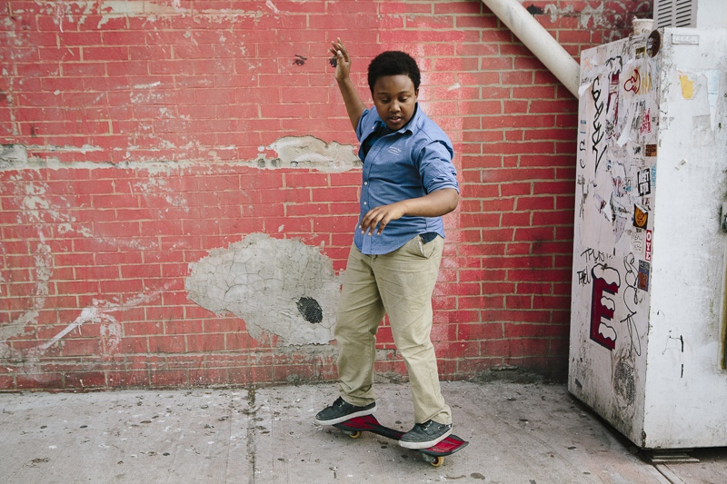 Justin, 14, plays on his skateboard as he waits for his brothers to bring out an after school snack from the corner bodega in Brooklyn, NY on May 20, 2015.