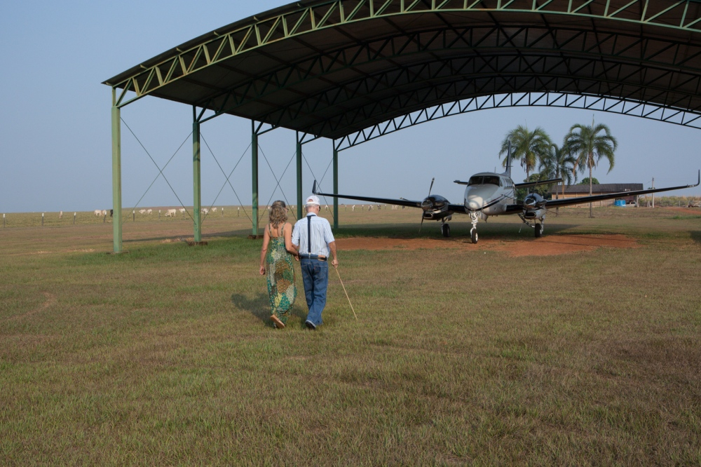 Antonio Ronaldo Rodrigues da Cunha, 80, one of the most important and traditional cattle breeders in the country, walks with his daughter to their private plane. Mr. Antonio Ronaldo is one of the pioneers in zebu cattle breeding in Brazil as well as one of the first to entry livestock in the state of Mato Grosso. Pontes e Lacerda, Mato Grosso, Brazil, 2015