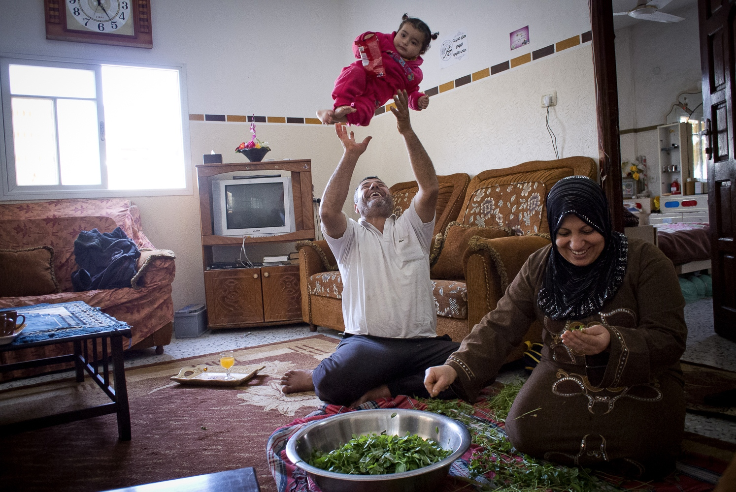 Nasser Abu Emeira at home with his wife and grand daughter preparing dinner in Beach Camp, Gaza City, Gaza Strip.