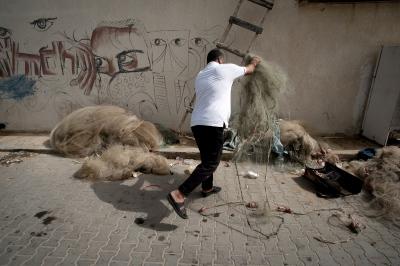 Nasser Abu Emeira throwing away broken nets outside his fishing shed at Gaza Port, Gaza Strip.