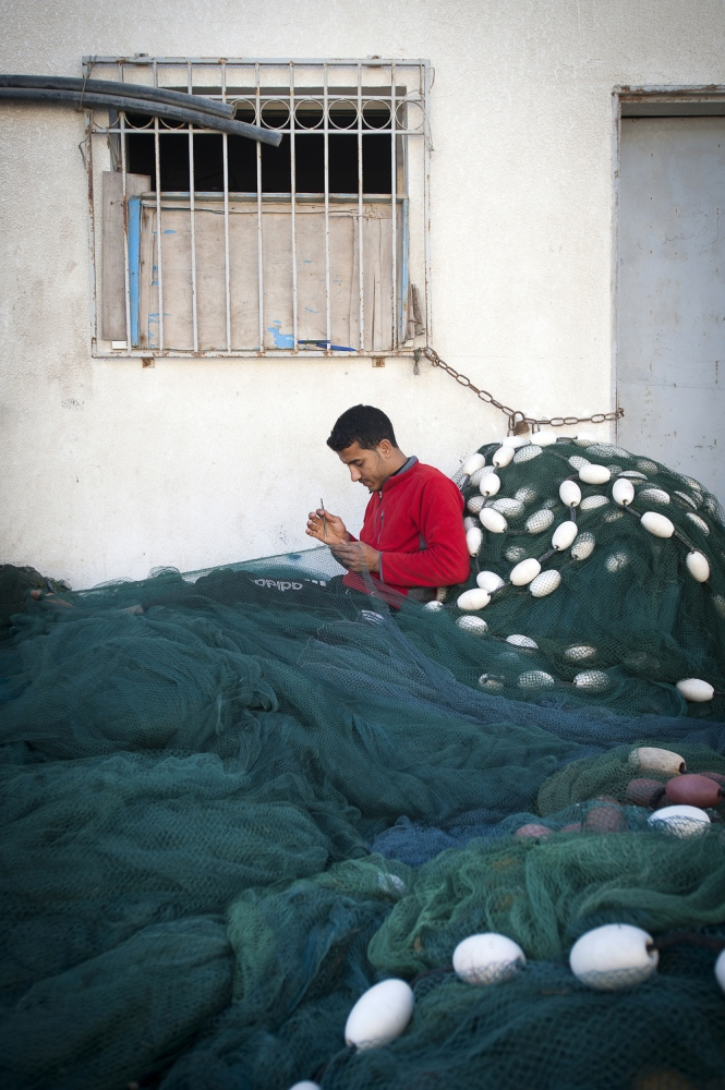 24 eyar old Achmed Abu Emeira mending fishing nets at Gaza Port, Gaza Strip, occupied Palestinian territories.
