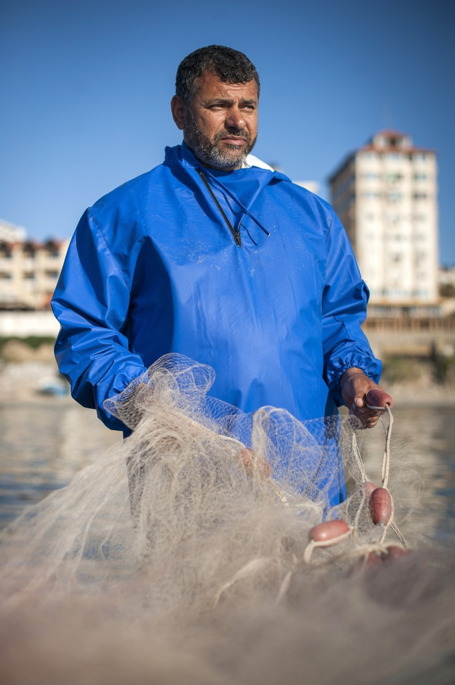 47 year old Gaza Fisherman Nasser Abu Emeira checking his fishing nets while in Gaza Port, Gaza Strip, occupied Palestinian territories.