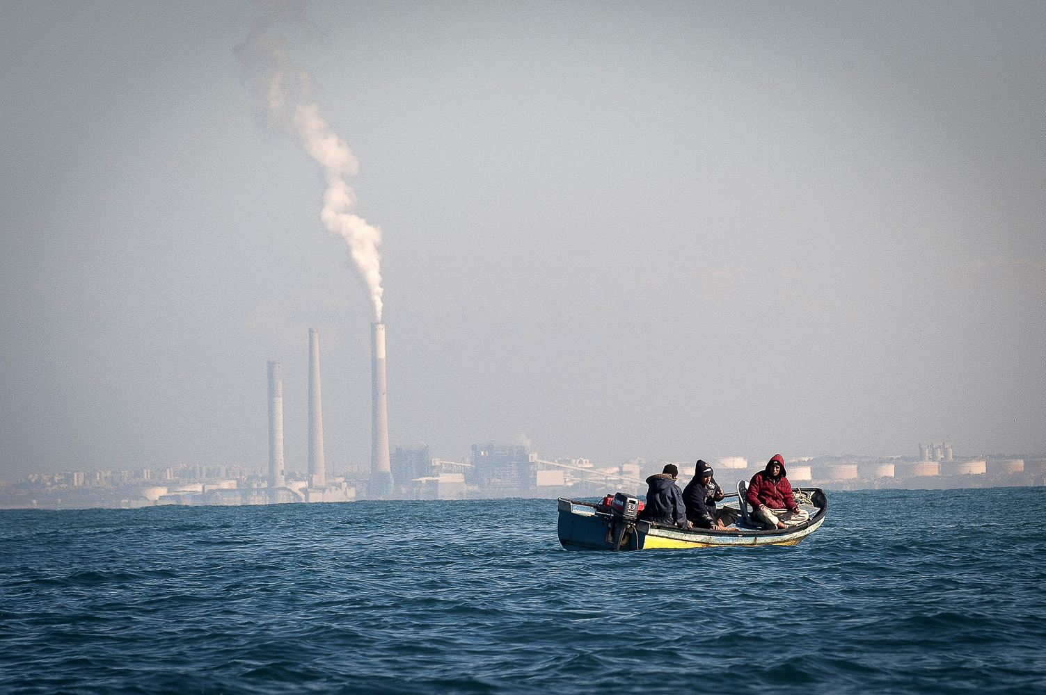 Line boat fishing off the Gazan coast. The chimney stacks behind the line boat are in Israel.