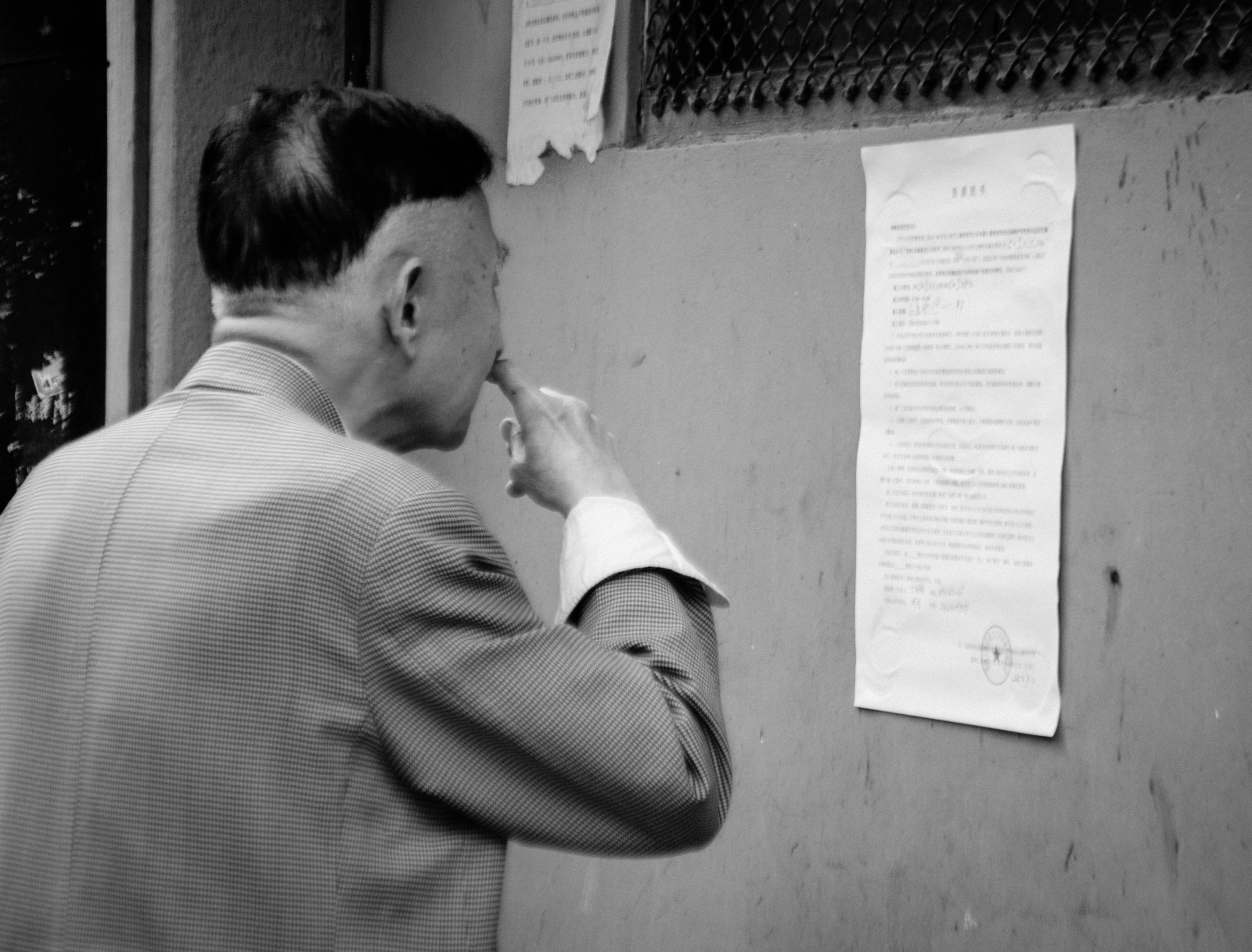A man reads an official eviction/relocation notice posted on a community wall in his neighborhood.