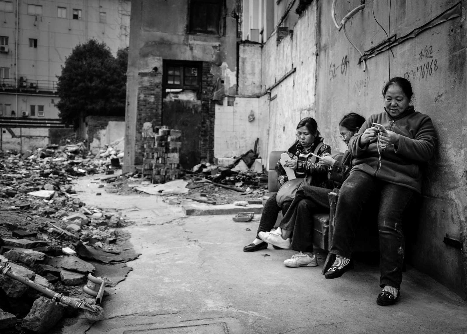 Communities live on, as these women continue their social sewing, piled much like the rubble atop a straggling sofa.