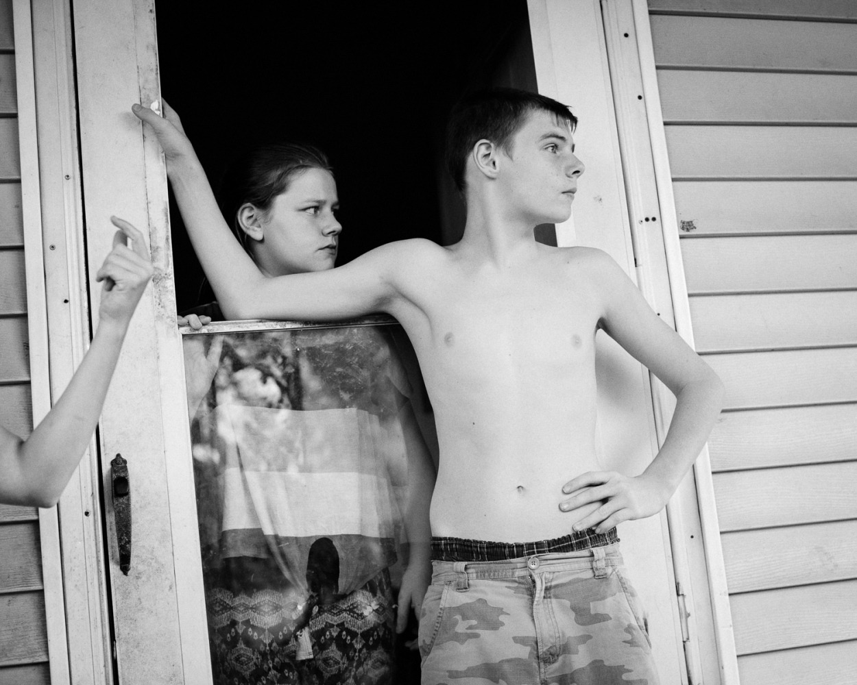 Kids watch from their front porch on Seventh Street in the East End neighborhood of Portsmouth. The East End has the city's highest crime rate. Many of its residents struggle with poverty and drug addiction.