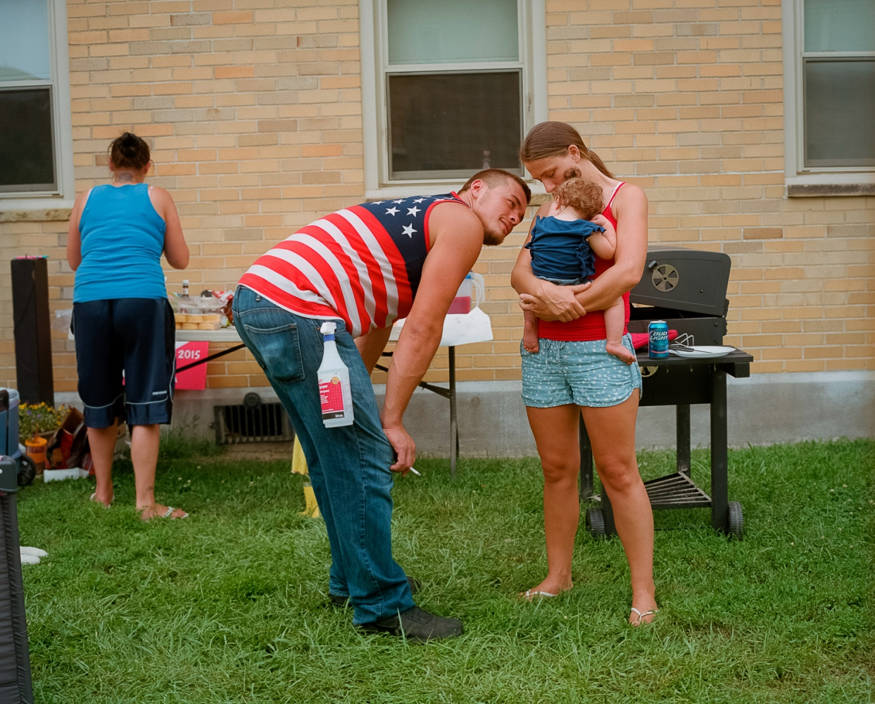 Levi and Nikki with their baby, Mazie, on the Fourth of July at the Wayne Hills apartment complex in Portsmouth. A subsidized housing project, Wayne Hills is known in the community for the prevalence of drug use among its residents. Both Levi and Nikki have steady jobs, and neither struggles with addiction.