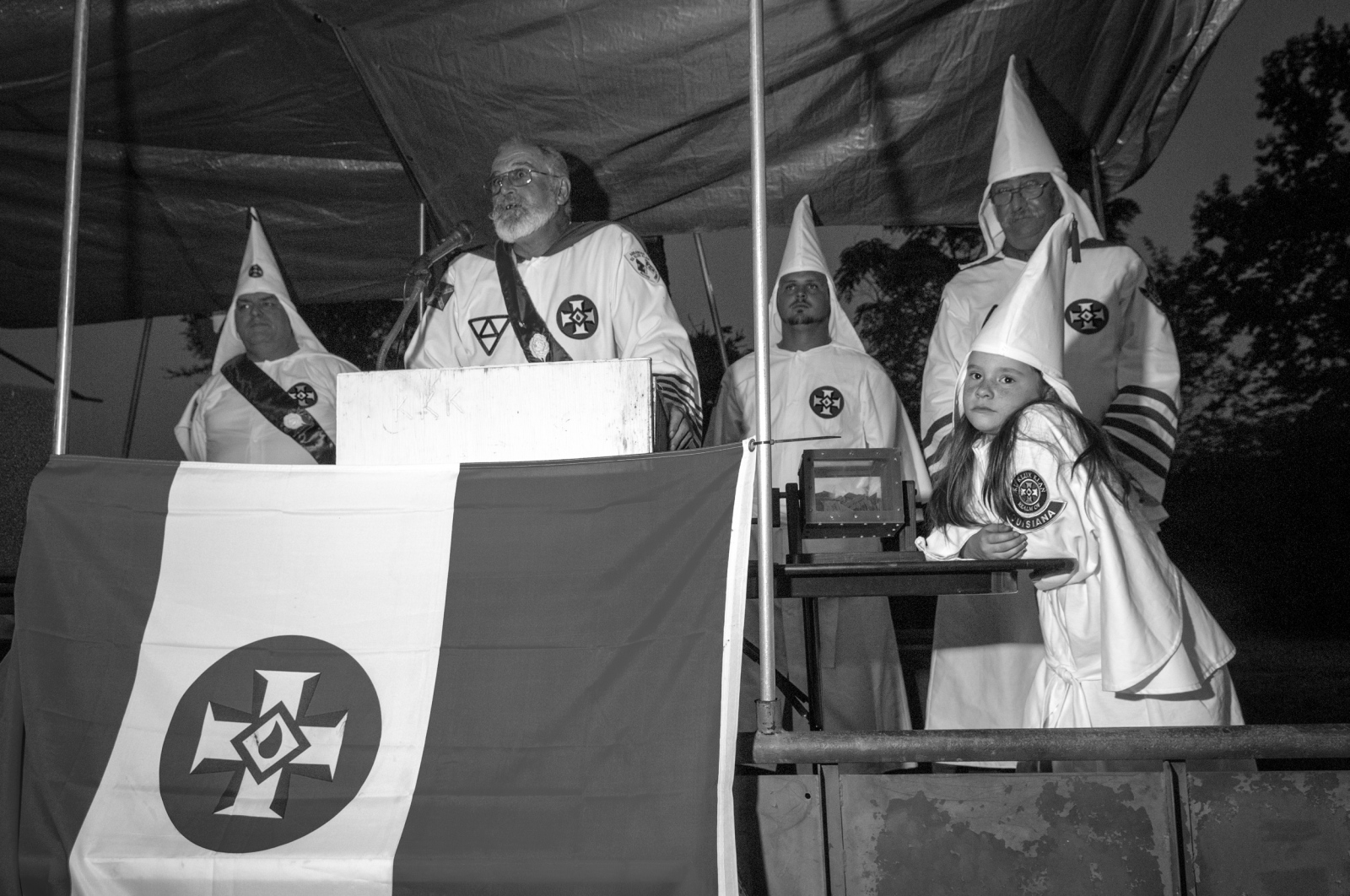 Arkansas.Members and supporting Klan realms from five different states came together for a two-day weekend of racial unity. The gathering included BBQ's, a raffle (shown here), fellowship, an award ceremony and a Klan naturalization. A historical cannon was fired every hour on the hour during daylight hours, until local neighbors complained. Saturday evening closed with a cross lighting ceremony which, according to Klan ideology, dispels darkness and ignorance. Due to a statewide burn ban; the lighting was carried out with Christmas tree lights.