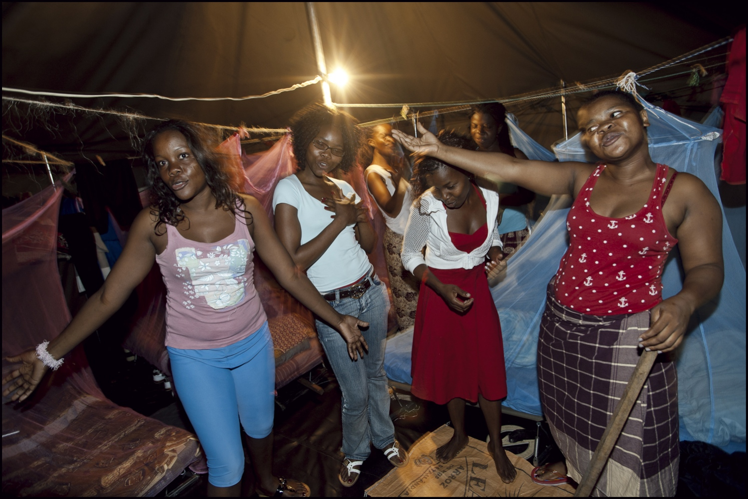 Relaxing in their tents in the evening, the womens section sing and dance to a popular Brazilian love song at Damo Camp Maputo Province, Mozambique.
