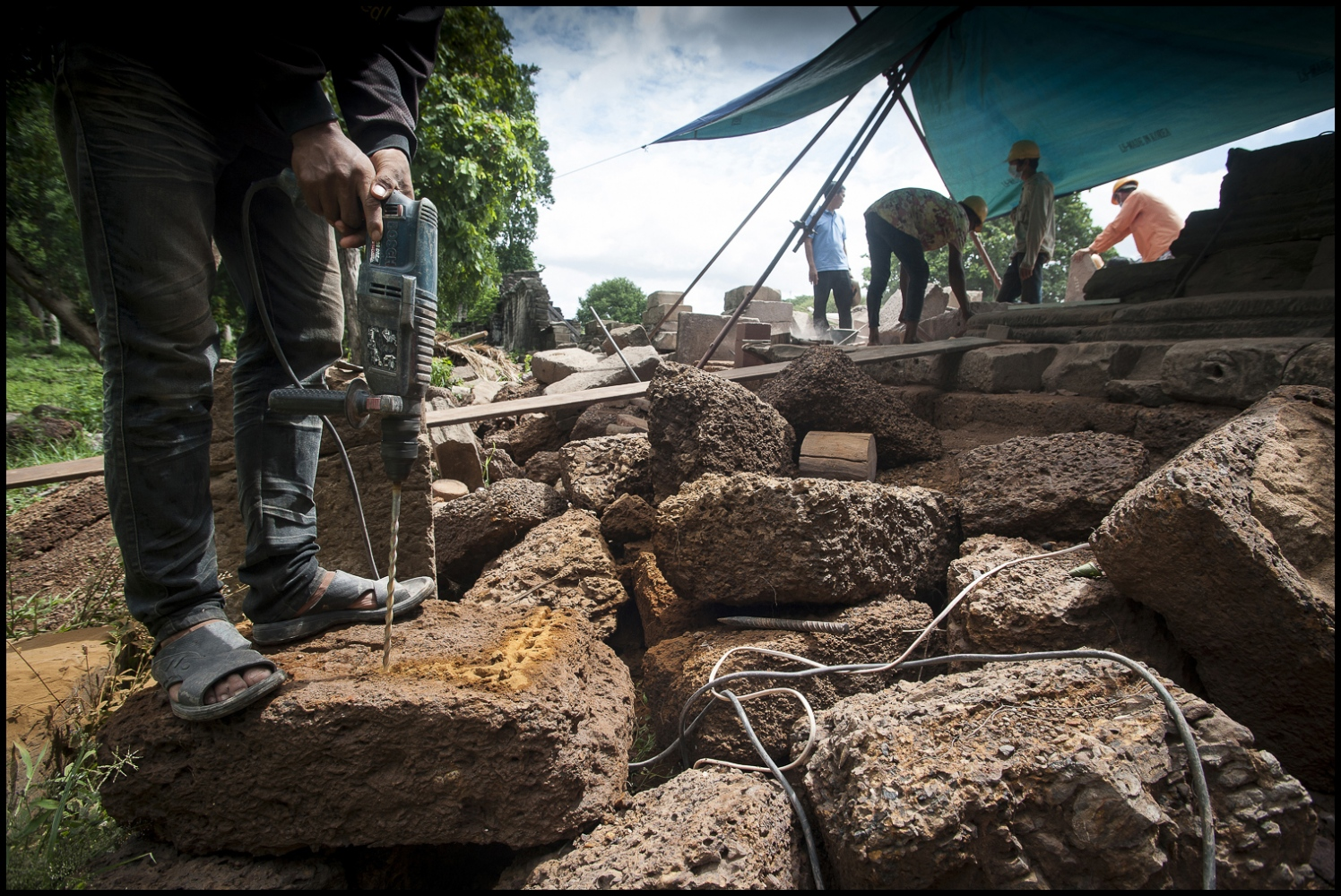 """Khmer stone masons at work on the laterite stones at the Banteay Chhmar Temple in Cambodia. Built by Khmer King Jayavarman 7th (1181-1219). They have spent the last 3 years painstakingly dismantling and rebuilding this 20 metre section of the temple ruins at Banteay Chhmar. John Sanday """"The Khmer stone masons have an affinity with the stone. They're allways touching it feeling for the accuracy of the join."""