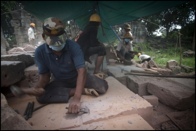 "Khmer stone masons working on the stone work to the Banteay Chhmar Temple in Cambodia. Built by Khmer King Jayavarman 7th (1181-1219). They have spent the last 3 years painstakingly dismantling and rebuilding this 20 metre section of the temple ruins at Banteay Chhmar. John Sanday ""The Khmer stone masons have an affinity with the stone. They're allways touching it feeling for the accuracy of the join."