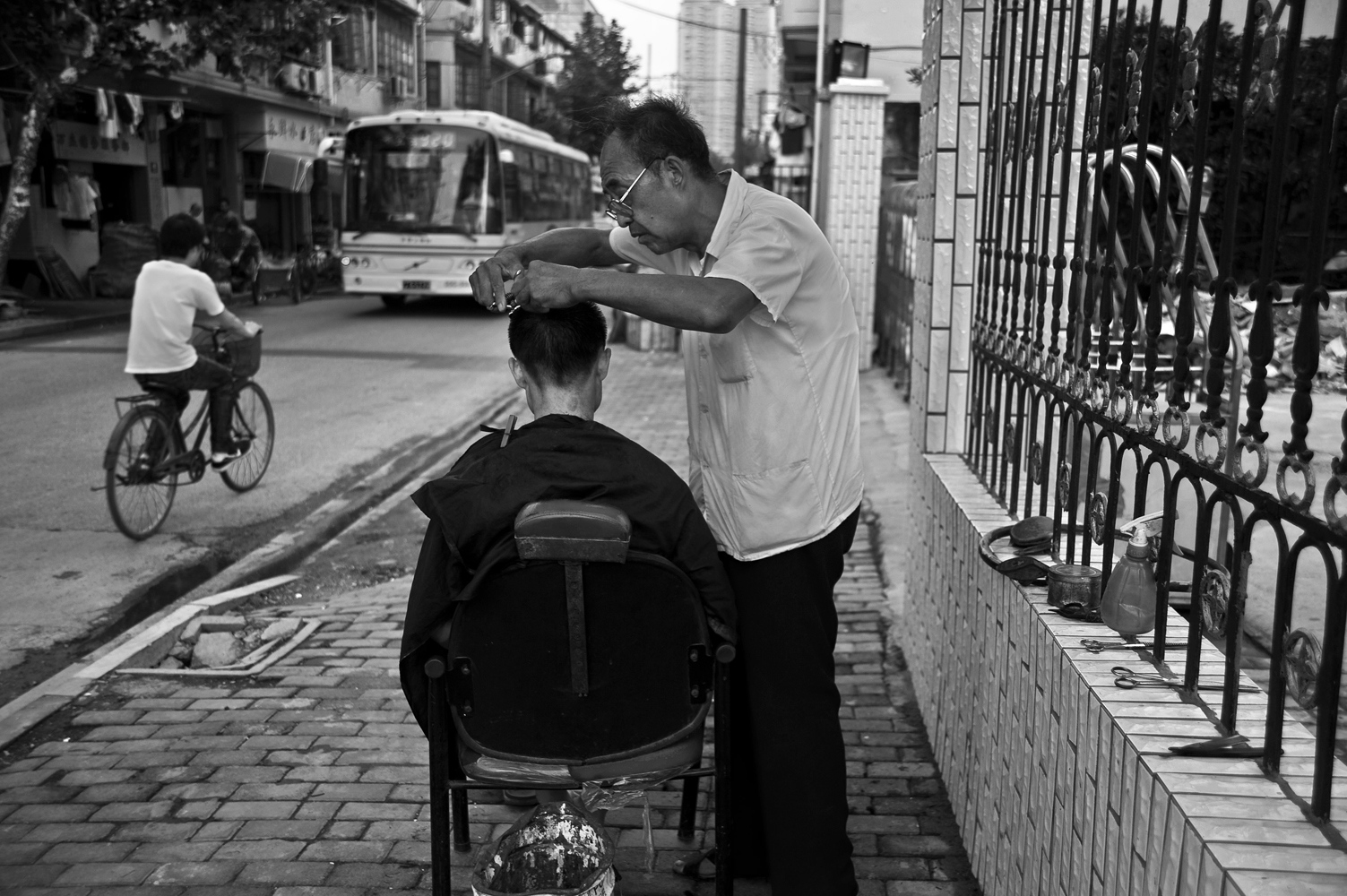As in other world capitals popular trades are facing commercial corporations, its days are numbered. Street Barber.
