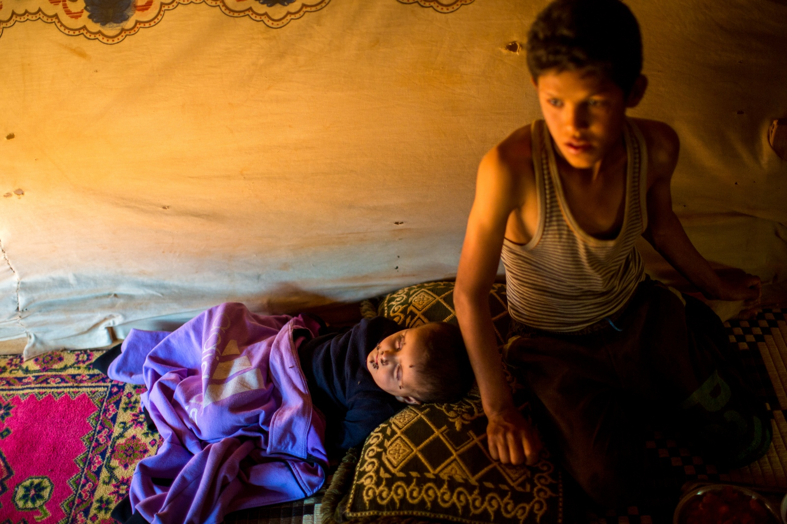 Bekaa Valley, LEBANON, September 5, 2014: Syrian refugee Jassem, 12, watches over his little brother, 3, as he sleeps in their tent in an informal settlement in Lebanon's Bekaa Valley. Jassem and his parents fled Syria in late 2011. They have been living in makeshift shelters ever since. The Lebanese government has refused to allow traditional refugee camps for Syrians in Lebanon, so many live in temporary shelters across the country.