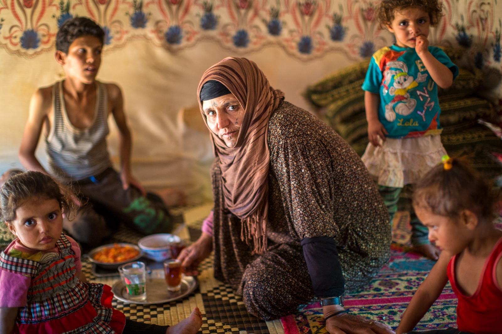 Bekaa Valley, LEBANON, September 5, 2015: Amina with four of her five children in their tent. She is the center of their lives as their father or other male figures are absent. Many refugee women are single parents as their husbands have gone missing or been killed in the Syrian war.
