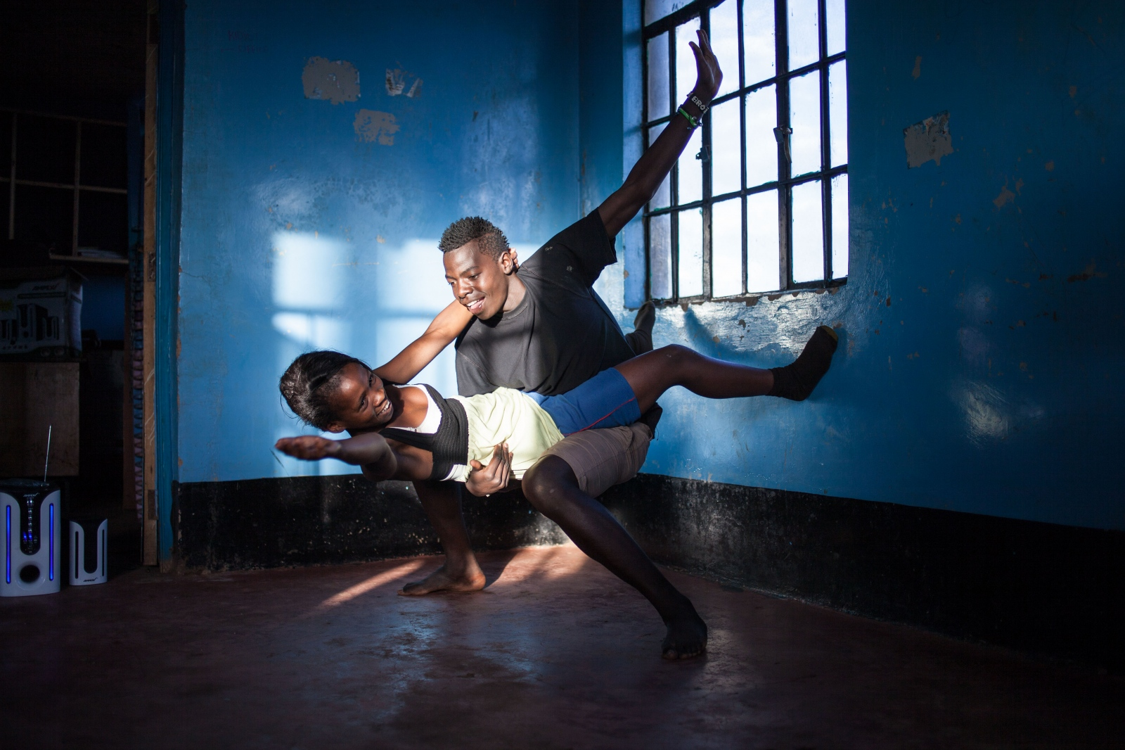 Kibera Slum, Nairobi, KENYA, November 06, 2013: Quintor Adhiambo (17) and Victor Odhiimbo (19) at dance rehearsals of Waasani theatre group. Quintor left school in 7th grade after her father passed away. Her mother is unemployed and couldn't afford to further pay for her education. Through support from the group, which kept her away from bad company, she is now attending a hairdressing course. Victor also had to leave school because his parents could not to pay for his school fees. He is now engaged in the theatre group and hopes to go back to school one day.