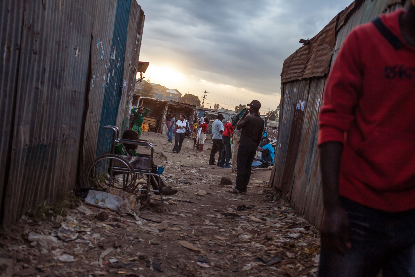 Sinai Slum, Nairobi, KENYA, October 29, 2013: A boy in a wheelchair is begging in an alleyway of Sinai Slum. Sinai is part of the Mathare slum collection with an estimated population of 600.000. Many children who live here do not attend school to help their struggling parents make an additional income.
