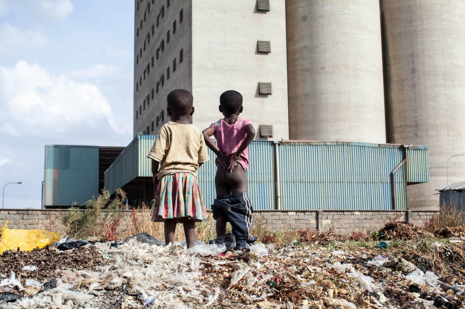 Sinai Slum, Nairobi, KENYA, October 29, 2013: Children standing on a pile of garbage, looking over the walls that seperate the slum from the city.