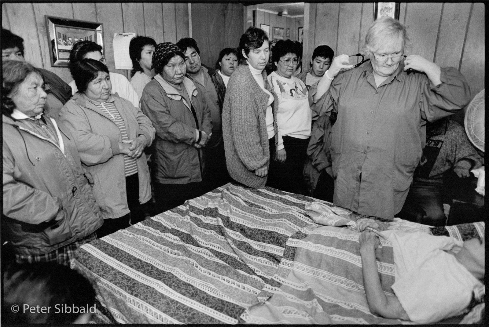 Close friends and family members gather at Mani Pasteen's deathbed to await nurse Barbara Lethbridge's official pronouncement of death, Sheshatshiu, Nitassinan/Labrador. Copyright Peter Sibbald, 1993.