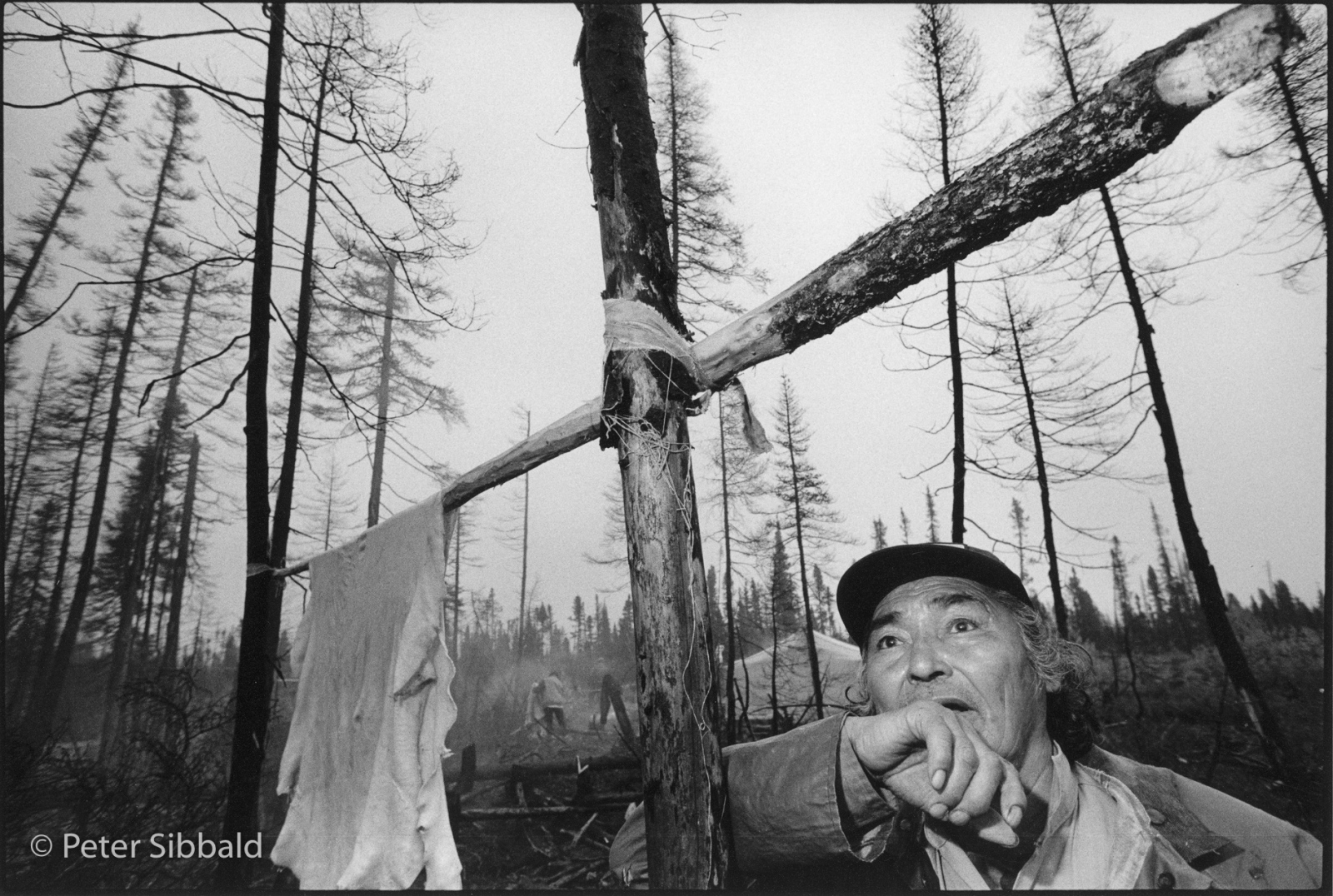 "Four Mile Road, near Sheshatshiu, Nitassinan /Labrador. On his way to check a caribou hide drying on a spruce frame, Innu elder Spatieish (Sabastian) Penunsi pauses to reflect on the roar of a near-flying fighter jet unseen through the fog. Since the mid-1980s the Innu have staged ongoing protests against the NATO fighter-jet training which variously the UK, The Netherlands, Germany, Italy, France, Belgium have conducted over land the Innu consider to be their ancestral hunting grounds. Innu elders like Penunsi say that they have observed negative impacts on wild-foul and caribou. Western scientific studies of such impacts have been relatively inconclusive or oddly tend to support the interests of their commissioners.. In country Spatieish is a consummate hunter and woodsman, but during the time I have also known him in the Sheshatshiu, he was often depressed, angry, and rarely sober, barely a shadow of the man I photographed that day. I've often thought of Sheshatshiu as the ""Village of Lost Souls"", though there have been indications that this has been changing for the better over time.."