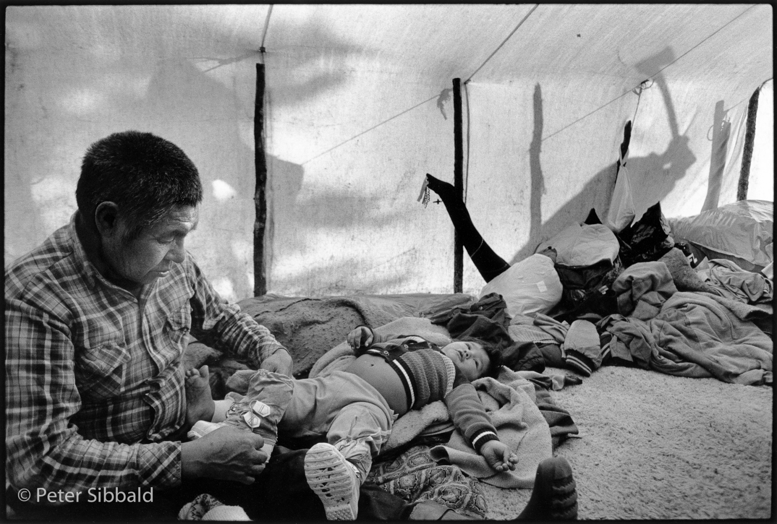 Penashue Camp, Mealy Mountains, Nitassinan/Labrador. Innu elder, Matthew Penashue dresses his adopted grandson during his morning routine in the country. Copyright Peter Sibbald, 1989.