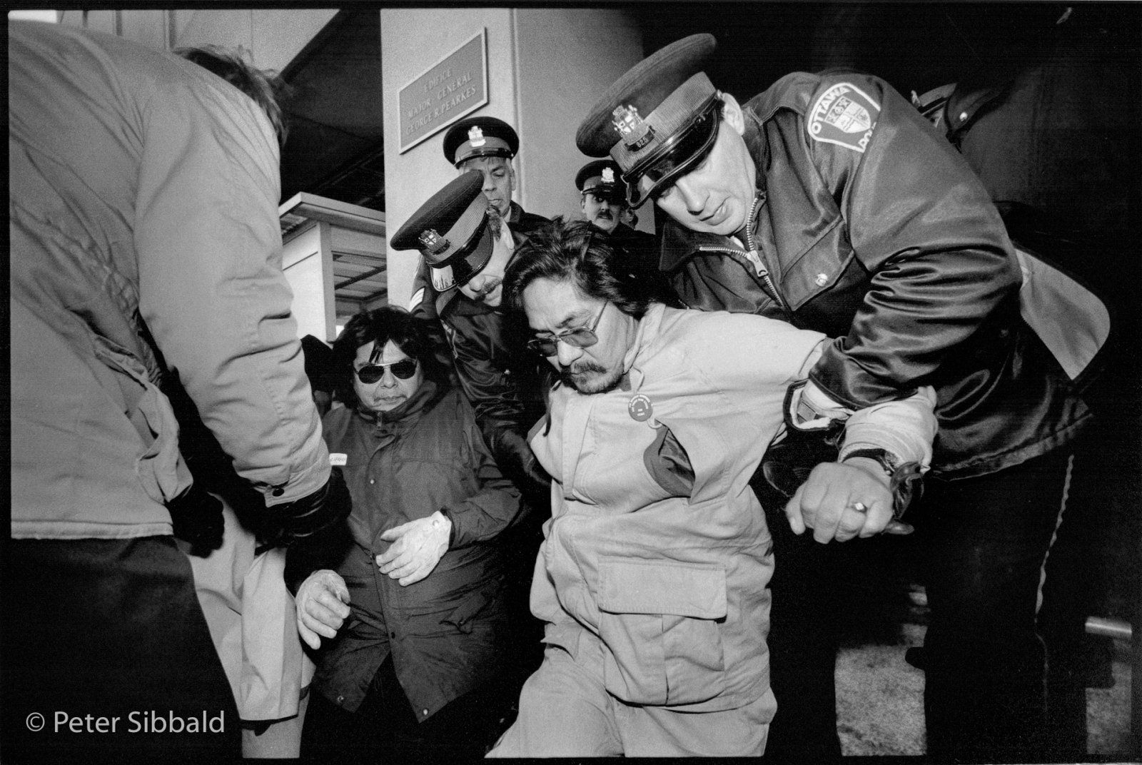 Ottawa, Canada. The Nation's Capital Innu spokesman Penote (Ben) Michel is arrested for blocking employee access to the Department of National Defence Headquarters during a Remembrance Day civil disobedience action protesting low-level flight training over Nitassinan. Copyright Peter Sibbald, 1990