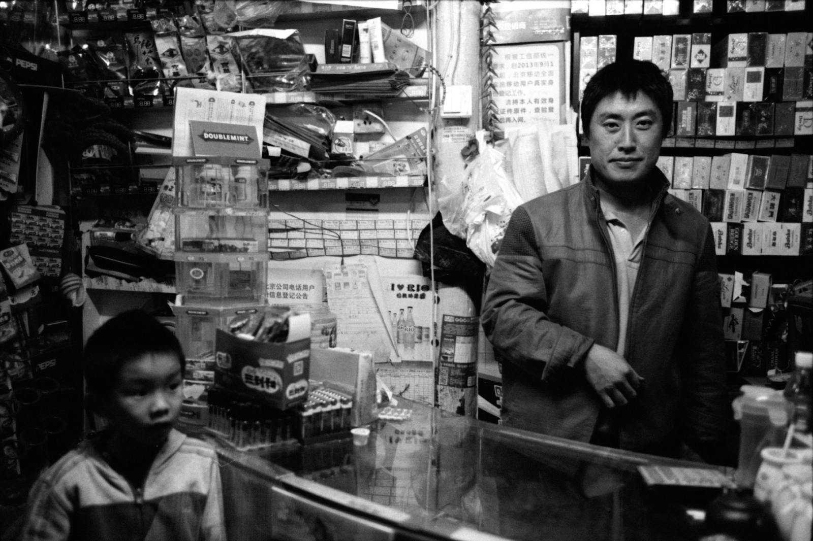 A man and a customer boy at a cigarette store.  Beijing, China. 2015