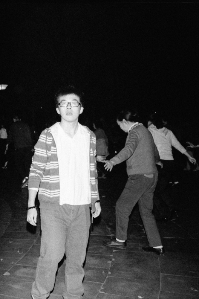 Beijin people dancing for exercise on a night near Xisi statation. Beijing, China. 2015