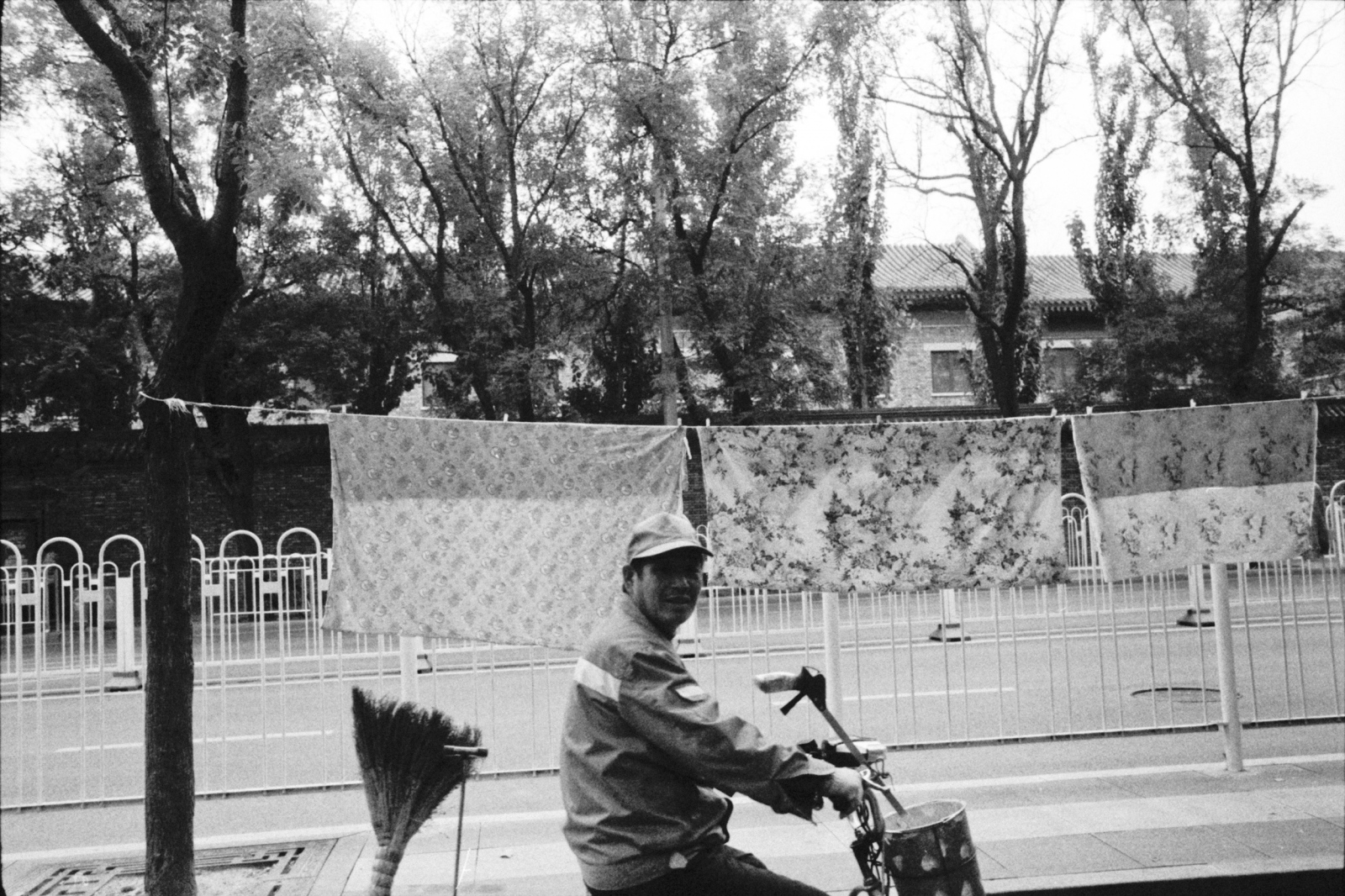 A worker smiled at me taking a photo of textiles, as he passed by. Beijing, China. 2015
