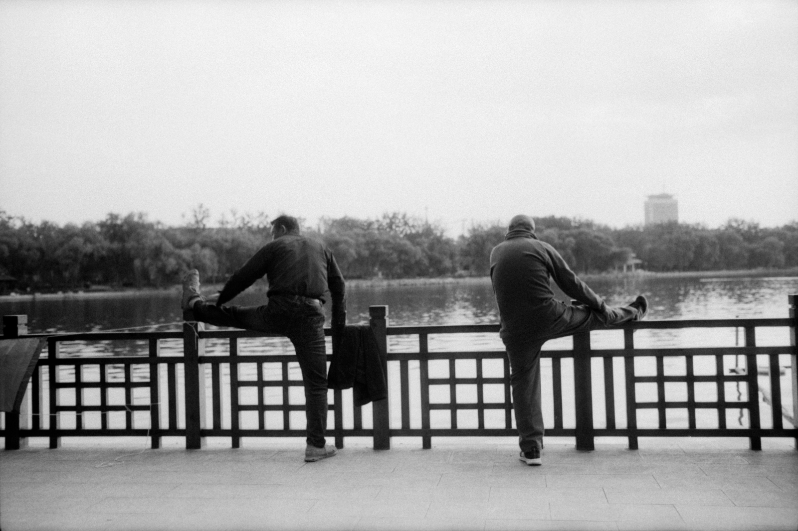Two men exercising by the lake in Yuyuantan park. Beijing, China. 2015
