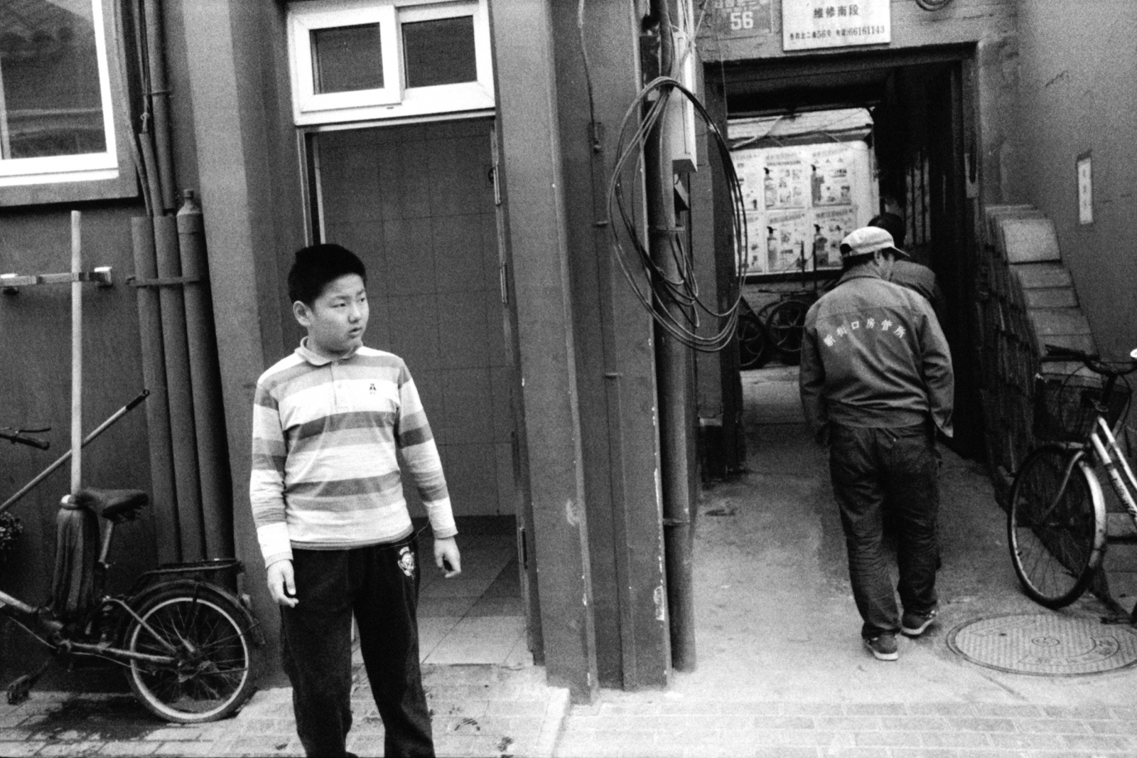 A boy stands in front of a public toilet.  Beijing, China. 2015