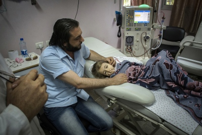 "Abdel Haleem with his 8 year old daughter Marah Diab at the Al Rantisi Paediatric Hospital in Gaza City. Marah has been undergoing dialysis for 2 years and shows symptoms of stunted growth, which common in child patients with renal failure. Marah's father says: ""She's top of her class at school and when she's finished here (dialysis takes approximately 3 hours) she'll return to her lessons."" At the al Rantisi (childrens) Hospital in Gaza City."