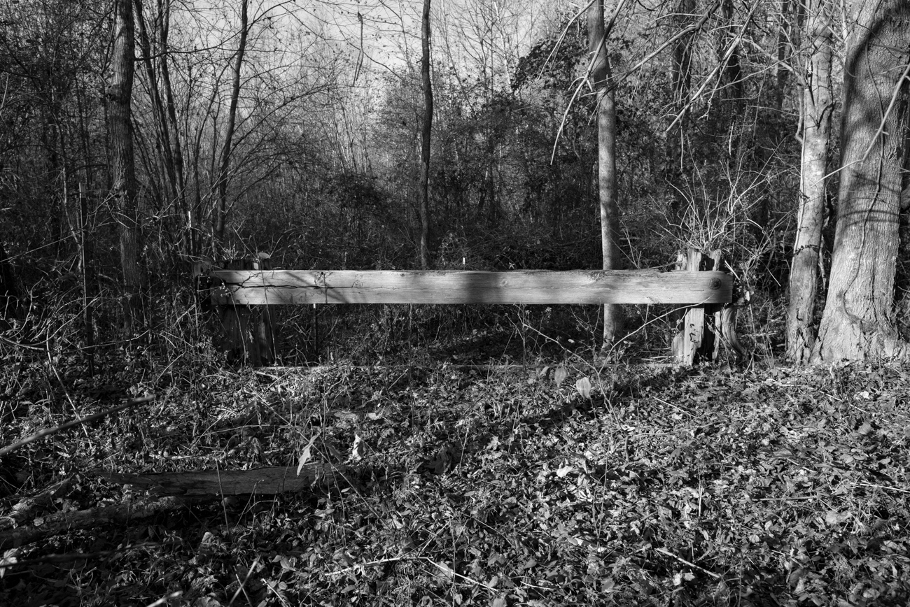 "Marshall County, MS. 12/2/2015. According to the great-grandson of the former property owner, a black man was tied to this railing of a wooden bridge in the 1960's and whipped by several members of the local Klan. He was accused of repeatedly stealing watermelons from the property adjacent to their family's cotton farm. Not long after, that same man was accused of assaulting a local white woman. The black offender was taken back to the bridge where he was whipped again, and then to a large oak tree, dubbed ""the hanging tree,"" a minute's walk down the road where he was subsequently lynched for his offenses… the lynching was unreported. In the late 1990's the great-grandson attempted to till the soil around ""the hanging tree"" in an effort to plant a flowerbed. The till broke and he temporarily abandoned the project. A few months later, during December of the year 1997 the tree was struck twice by lighting during a winter lighting storm. The large oak burned for two days and his neighbor (a late former slave who lived to be over 100-years old and who was familiar with the lynching) somewhat panic stricken, warned the grandson that he woke up some ""bad medicine."" The bridge was truncated in 1977 after a new highway was constructed."