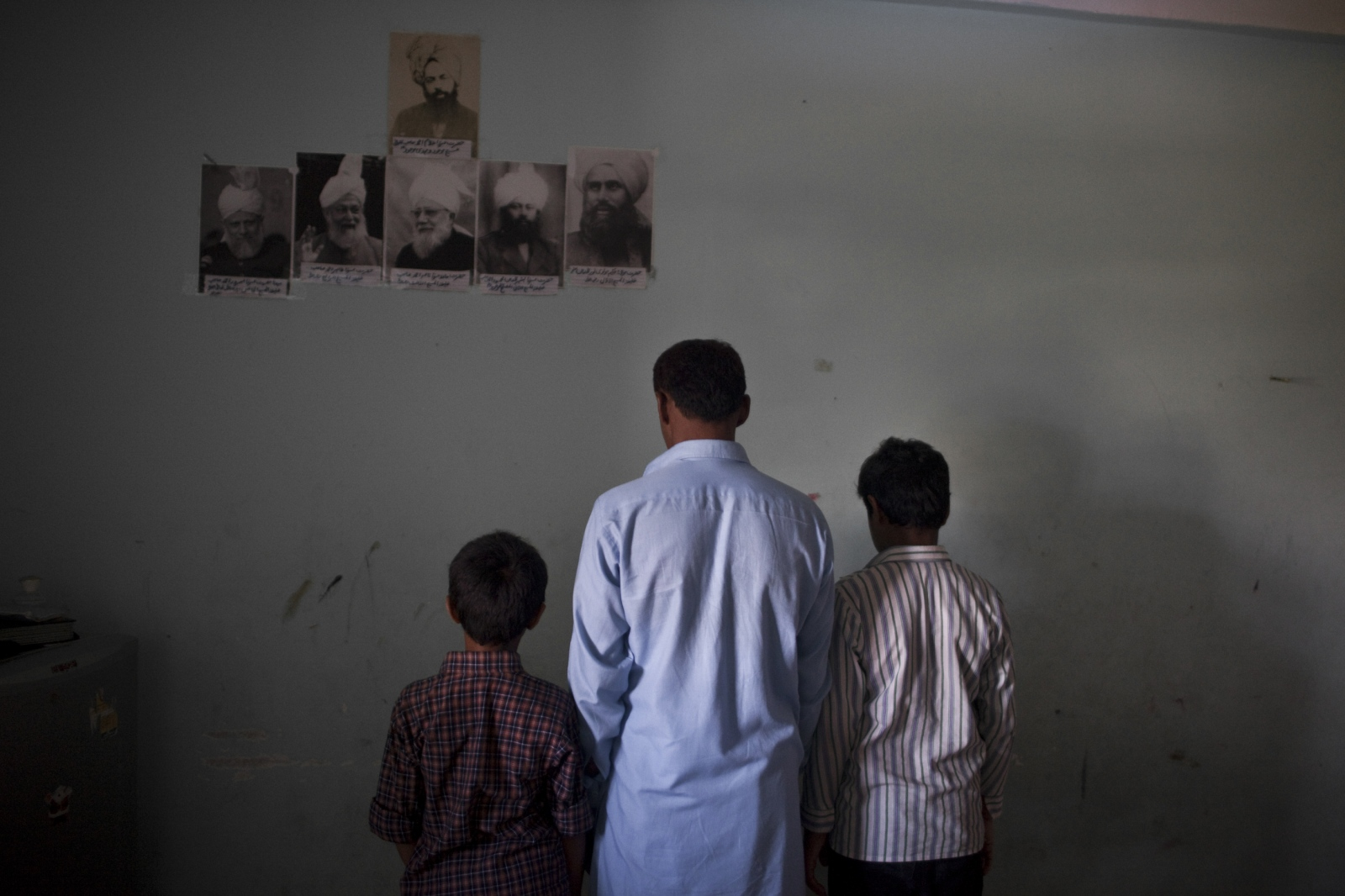 A father and his two sons from Islamabad, Pakistan, seeking asylum on the outskirts of Bangkok, practice their faith inside their one room apartment. They are Ahmadi Muslims, a religious minority, who is often targeted and discriminated against by other Muslims in Pakistan. Apr. 2015