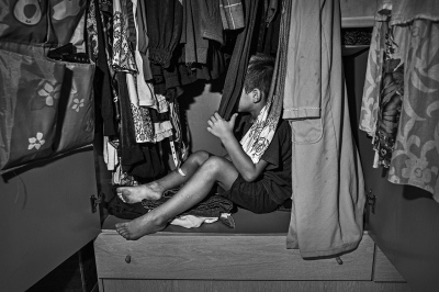 A child plays in the closet of a poor, unemployed family in a depressed neighborhood of Seville.