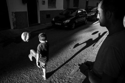 An unemployed father of a family of humble origins watches his son play soccer from the doorway of their house on a street in a depressed neighborhood of Seville.