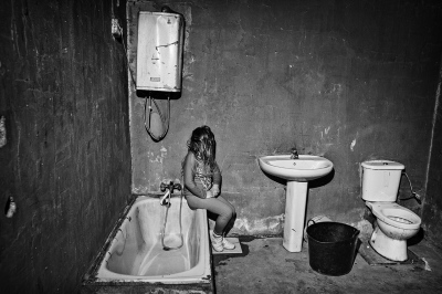 A girl in a bathroom of a prefabricated house in a shantytown of Seville.