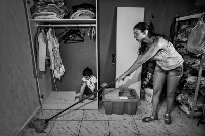 A woman from a working class district of Seville scrubs the floor of her home while her son plays on the floor.