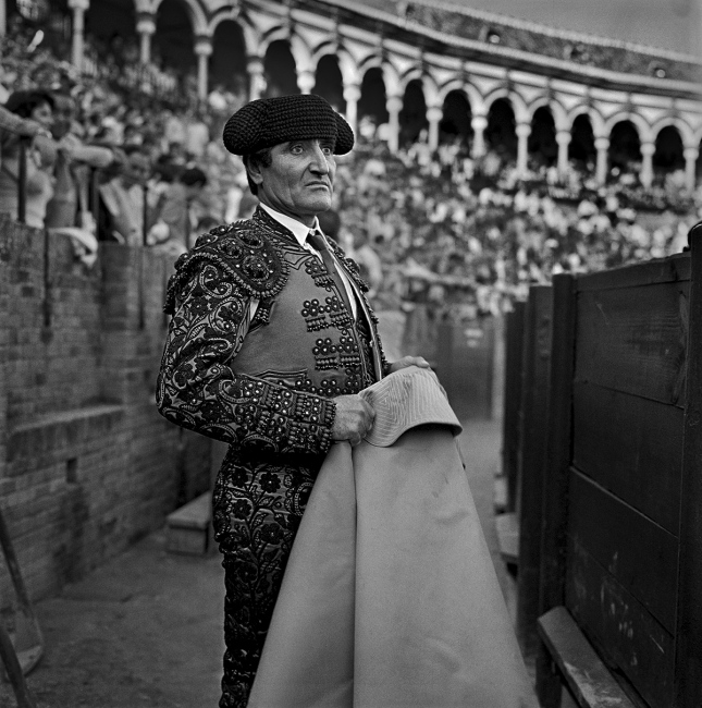 A banderillero worriedly looks on as the fight unfolds. Seville.