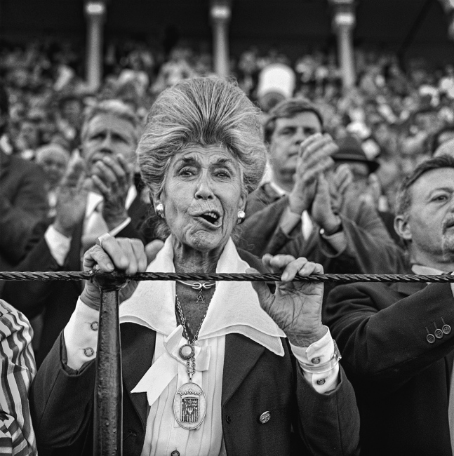 From the barrier a woman shouts and cheers at the bullfighter's performance. Seville.