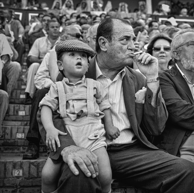 A bullfight enthusiast with his grandson during an afternoon of bullfighting at the Seville Fair.