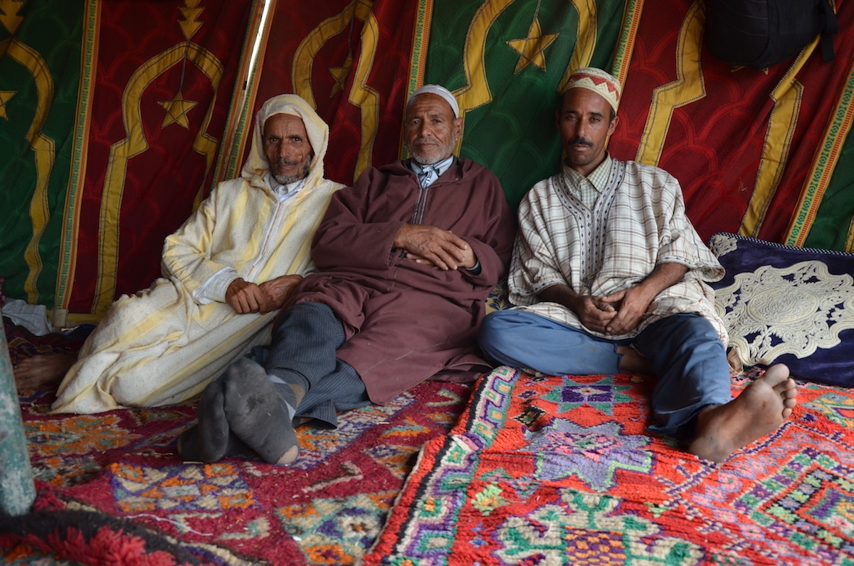 Riders relaxing on the carpets of their Cherifian tent after a series of rides. Oued Merzeg, Morocco