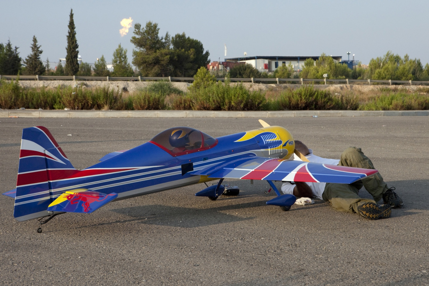 Model airplane enthusiasts use an abandoned road to a settlement as a runway. In the background is the flare from Israel's 'Meged 5' Gas and oil plant. The Green Line runs from left to right through the picture.