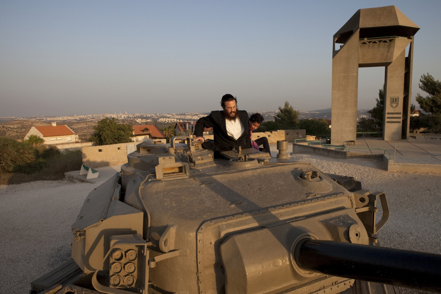 An orthodox man climbs into a tank, at a monument in the middle of the Israeli settlement of Har Adar ('the Radar' - an old British radar post). The Green Line runs between Har Adar and the Israeli villages on the Horizon.