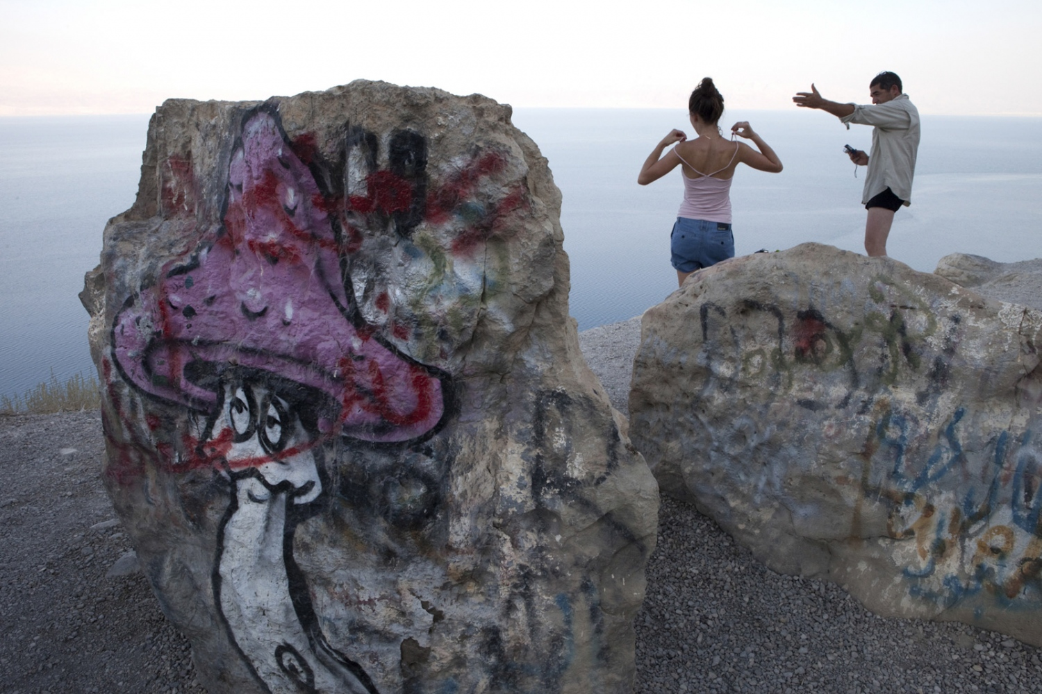 Israeli Tourists pose for photos at a viewing point on route 90 on the coast of the Dead Sea. The far shore is Jordan.