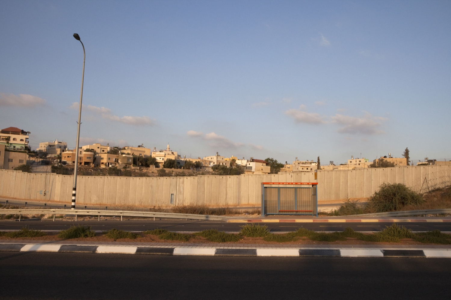 An Israeli Bus stop on route 358. The Palestinian village of Beit Atwa is located behind the barrier and the Green Line