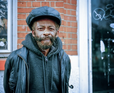 This is Ras Imruh Asha, he is a reggae artist who has been making music for the last thirty years. When I take his photograph he is with a friend who his selling his latest album,  Backs Against The Wall  along with the usual incense sticks, on the corner by the station.