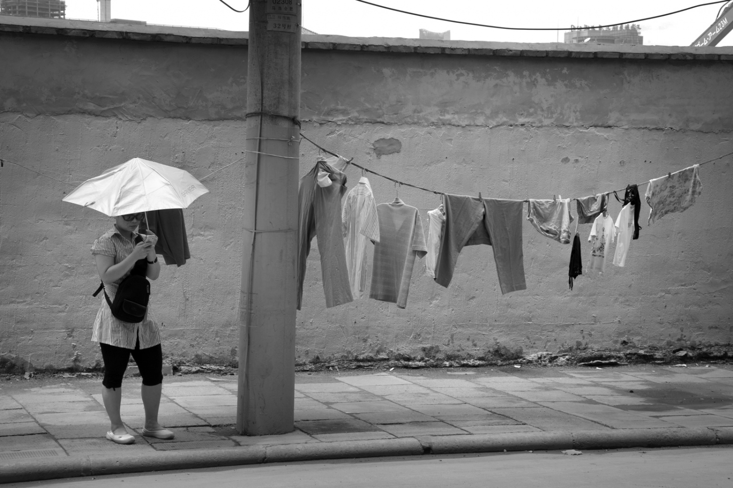 Hang clothes on the street is another symbol of identity of Shanghai. And using umbrellas to sun protect.